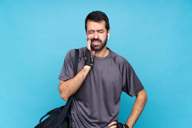 Młody sporta mężczyzna z brodą nad odosobnionym błękitnym tłem z bólem zęba