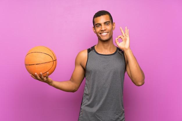 Młody sporta mężczyzna z piłką koszykówka nad odosobnioną purpury ścianą pokazuje ok znaka z palcami