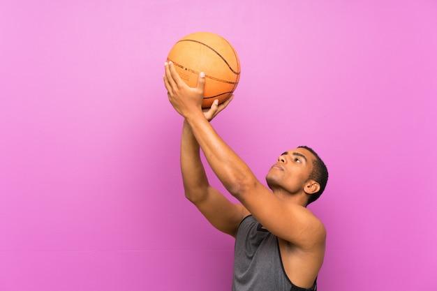 Młody sporta mężczyzna z piłką koszykówka nad odosobnioną purpury ścianą