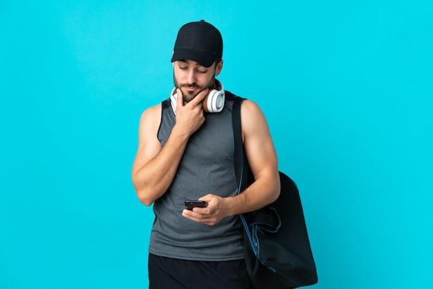 Młody sporta mężczyzna z sport torbą odizolowywającą na błękit ścianie myśleć i wysyła wiadomość