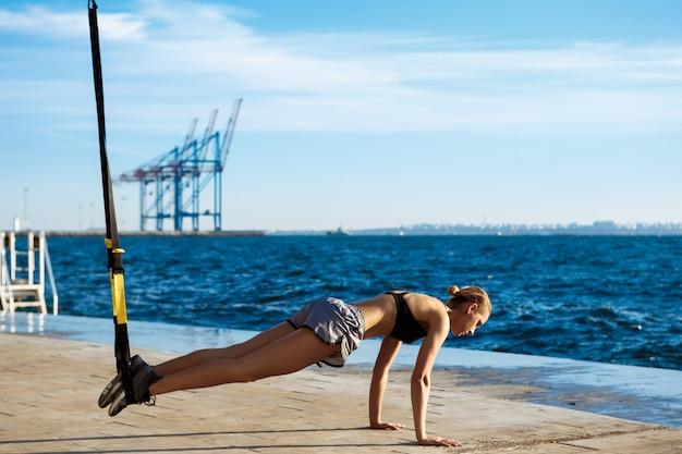 Młody sportive kobiety szkolenie z trx blisko morza w ranku.