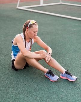 Młody sportive siedzi na trawie i sprawdzania czasu