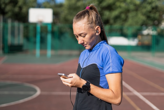 Młody sportive sprawdzanie telefonu komórkowego po treningu