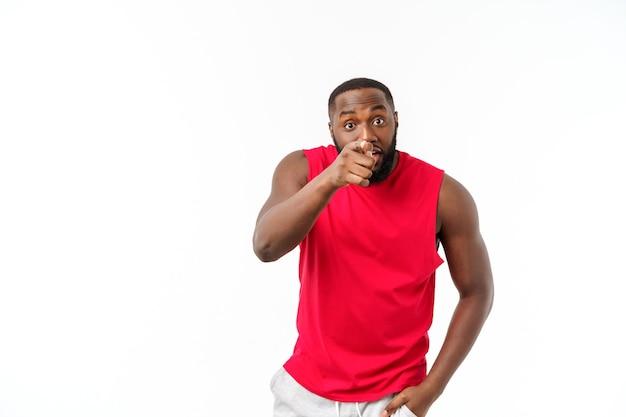 Młody sportowiec african american, wskazując palcem ze zdziwieniem, czuje się dobrze i pomyślnie.