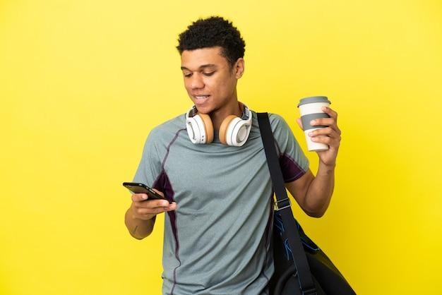 Młody sportowiec afroamerykanin z torbą sportową na żółtym tle trzymający kawę na wynos i telefon komórkowy