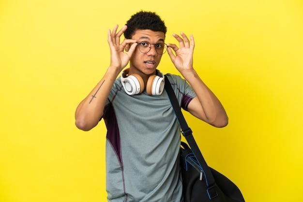 Młody sportowiec afroamerykanin z torbą sportową na żółtym tle w okularach i zaskoczony