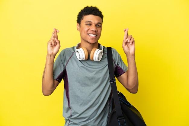 Młody sportowiec afroamerykanin z torbą sportową na żółtym tle ze skrzyżowanymi palcami