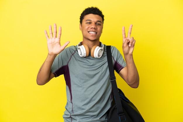 Młody sportowiec afroamerykanin ze sportową torbą na białym tle na żółtym tle, licząc siedem palcami