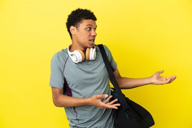 Młody sportowiec afroamerykanin ze sportową torbą na białym tle na żółtym tle z niespodzianką wyrazem twarzy