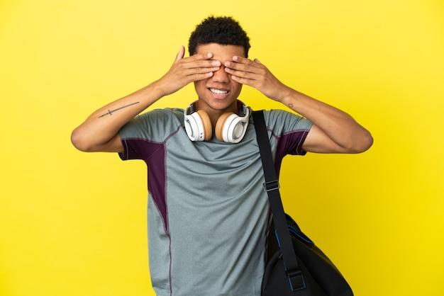 Młody sportowiec afroamerykanin ze sportową torbą na białym tle na żółtym tle zakrywającym oczy rękami