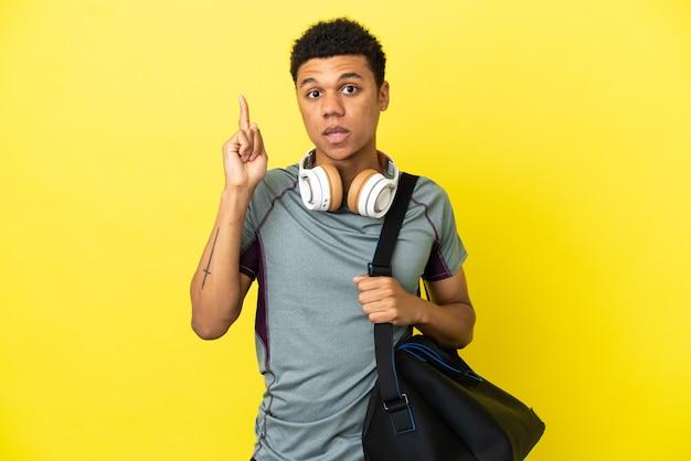 Młody sportowiec afroamerykanin ze sportową torbą na żółtym tle, myślący o pomyśle wskazującym palec w górę