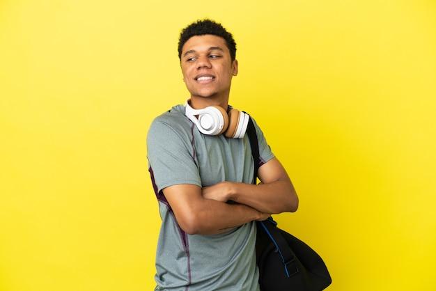 Młody sportowiec afroamerykanin ze sportową torbą na żółtym tle z rękami skrzyżowanymi i szczęśliwymi
