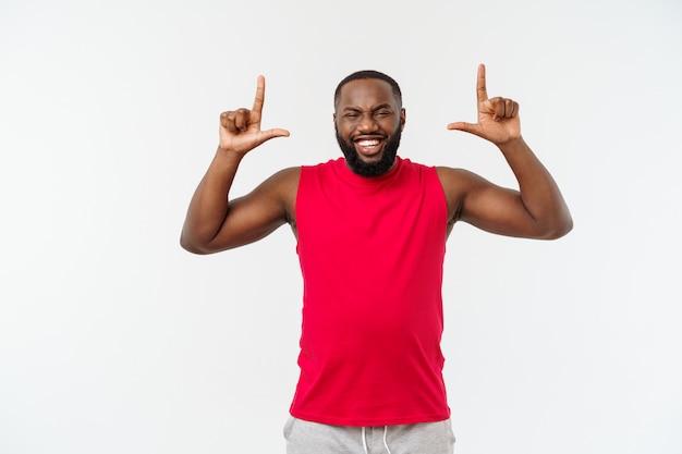 Młody sportowiec afroamerykanów wskazując palcem z zaskoczony, czuje się dobrze i dostatnio