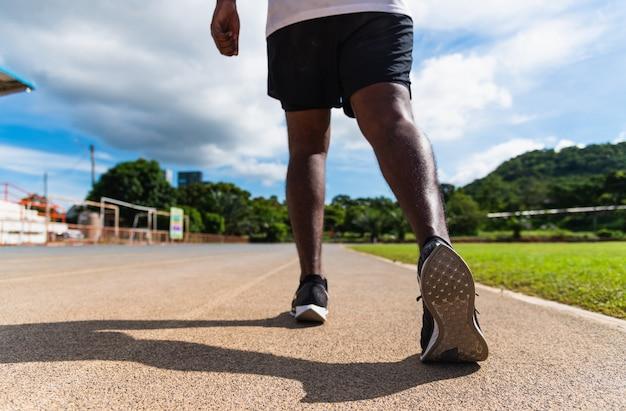 Młody sportowiec biegacz człowiek nosić stopy aktywne gotowe do biegania na świeżym powietrzu na drodze linii bieżni