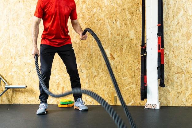 Młody sportowiec ćwiczący z linami w siłowni