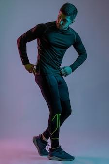 Młody sportowiec demonstruje swoje mięśnie w pozie kulturysty