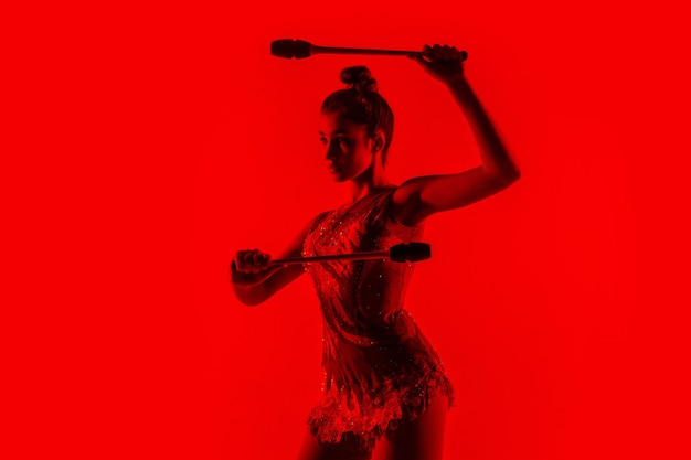 Młody sportowiec gimnastyka na białym tle na ścianie czerwony studio