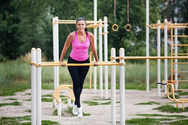 Młody sportowiec jest zaangażowany w poziome paski na ulicy.
