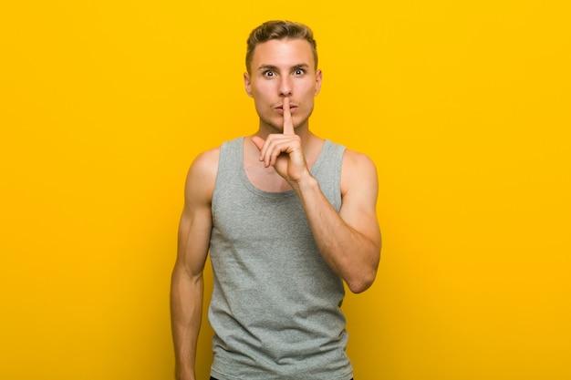 Młody sportowiec kaukaski, trzymając w tajemnicy lub prosząc o ciszę.