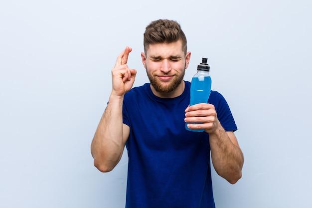 Młody sportowiec kaukaski trzymający napój izotoniczny trzymający kciuki za szczęście