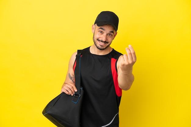Młody sportowiec kaukaski z torbą sportową na żółtym tle robi gest pieniędzy