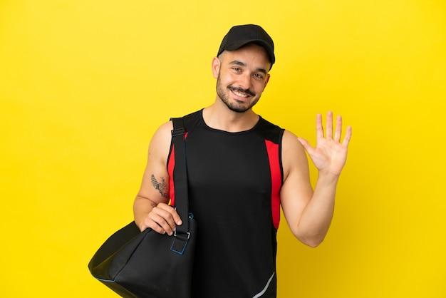 Młody sportowiec kaukaski ze sportową torbą na żółtym tle pozdrawiający ręką ze szczęśliwym wyrazem twarzy