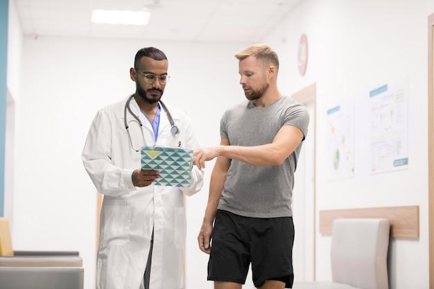 Młody sportowiec konsultuje się ze swoim lekarzem, wskazując punkt recepty w dokumencie medycznym w klinikach