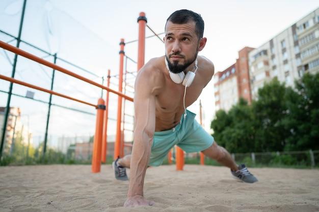 Młody sportowiec latem robi pompki na piasku na jednej ręce. sport, fitness, koncepcja street treningu