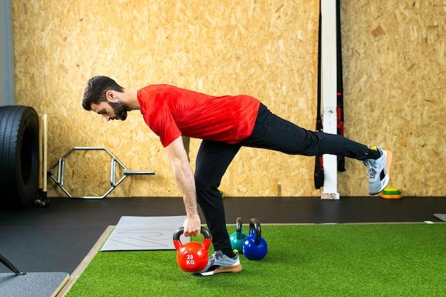 Młody sportowiec mężczyzna chwyta ciężki kettlebell na betonowej podłodze podczas treningu w podnoszeniu ciężarów w siłowni