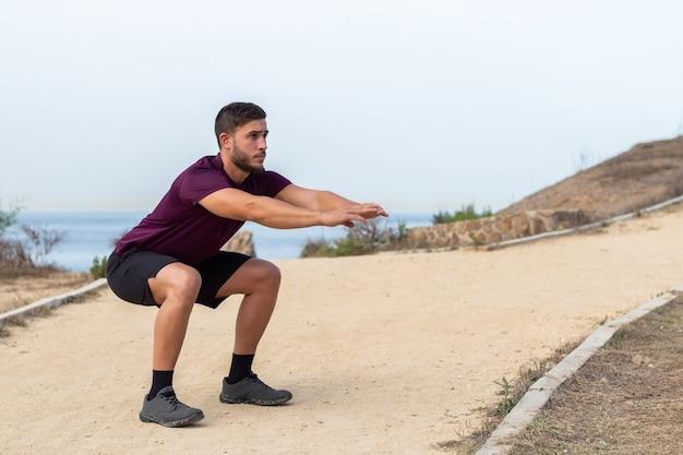 Młody sportowiec mężczyzna robi przysiady na świeżym powietrzu