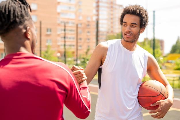 Młody sportowiec międzykulturowy z piłką ściskającą rękę swojego towarzysza przed lub po grze w koszykówkę na korcie