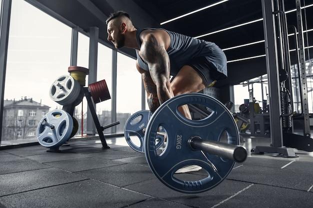 Młody sportowiec mięśni ćwiczy podciąganie na siłowni ze sztangą