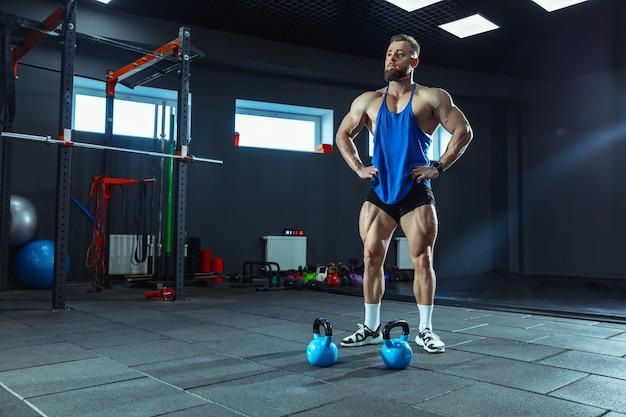 Młody sportowiec mięśni, trening w siłowni, ćwiczenia siłowe