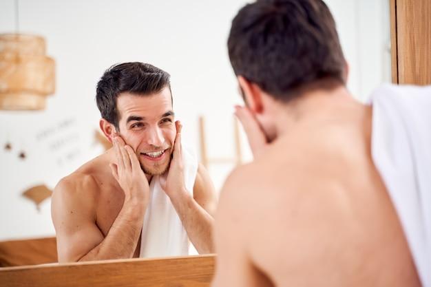 Młody sportowiec myje twarz i stoi z ręcznikiem na ramionach przed lustrem w łazience