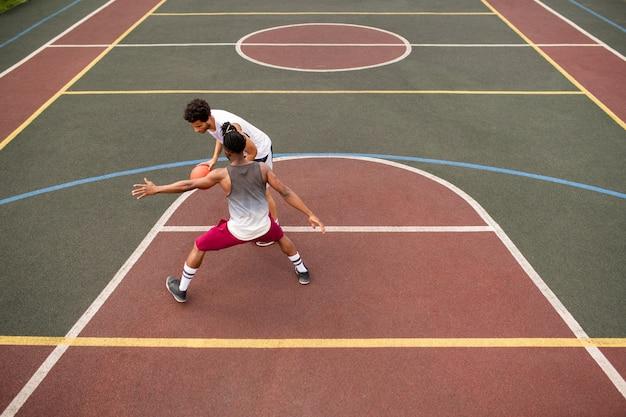 Młody sportowiec, niosący piłkę, próbujący rzucić nią nad rywala, grając w koszykówkę na korcie