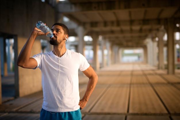 Młody sportowiec pijący wodę po ciężkim treningu