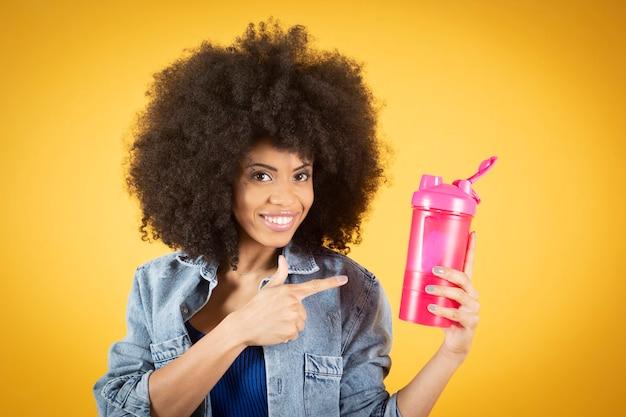 Młody sportowiec relaks na podłodze i picie smoothie na żółtym tle, szczęśliwy mieszany afrykański