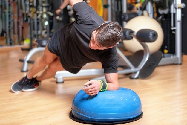 Młody sportowiec robi ćwiczenia abs na piłkę jako część treningu kulturystycznego.