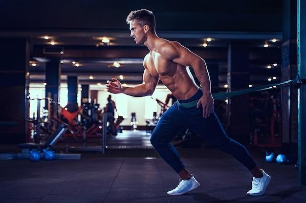 Młody sportowiec robi ćwiczenia z opaską.