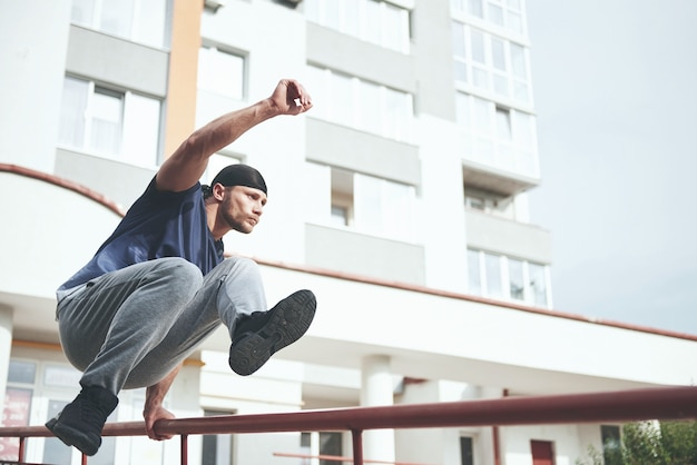 Młody sportowiec robi parkour w mieście.