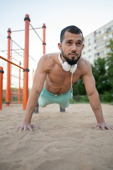 Młody sportowiec robi pompki i słucha muzyki w słuchawkach. sport, fitness, koncepcja street treningu