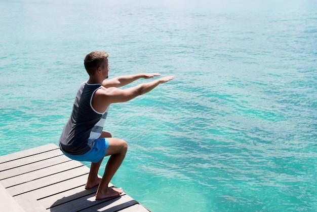 Młody sportowiec robi przysiady na morskim doku. zdrowy styl życia latem.
