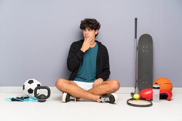 Młody sportowiec siedzi na podłodze wokół wielu elementów sportowych myśląc pomysł
