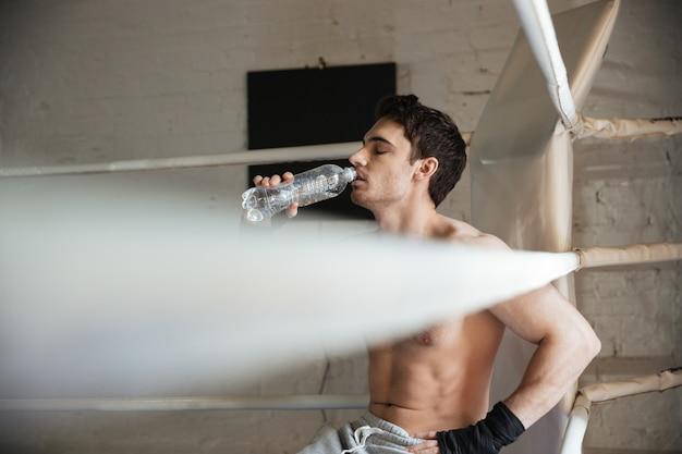 Młody sportowiec siedzi w ringu i picia