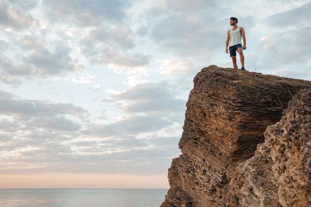 Młody sportowiec stojący na górskiej skale nad morzem i patrzący na zachód słońca