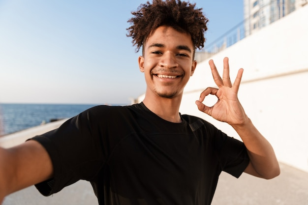 Młody sportowiec stojący na plaży na plaży zrób selfie aparatem pokazując dobry gest