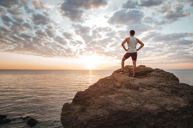 Młody sportowiec stojący tyłem na górskiej skale nad morzem i patrzący na zachód słońca