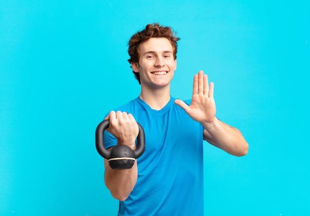 Młody sportowiec uśmiechający się radośnie i radośnie, machający ręką, witający i pozdrawiający lub żegnający. koncepcja hantle