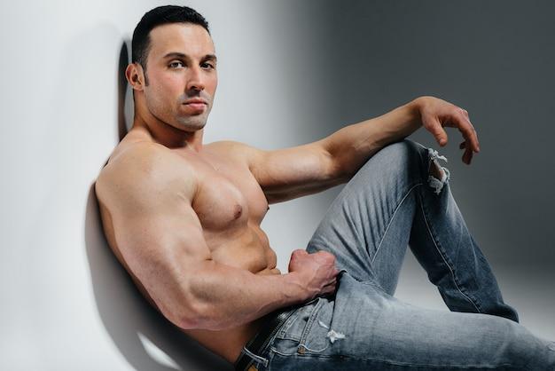 Młody sportowiec w dżinsach pozuje, siedząc w studio