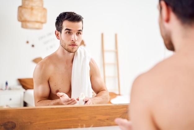 Młody sportowiec z balsamem w dłoniach i ręcznikiem na ramionach stoi przed lustrem w łazience